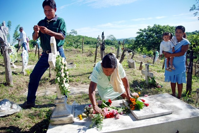Family members prepare the grave site of their deceased love one in preparation for the Day of the Dead celebration. Photography by Jay Dunn/www.JayDunn.org